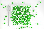Large Pile Of Green Colored Pills On White Plate