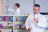 Concentrating pharmacist reading label on medicine jar in the pharmacy