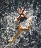 Young woman dancer jumping. On grunge wall background.