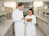 Team of pharmacists looking at clipboard at the laboratory