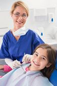 Smiling pediatric dentist with a happy young patient in dental clinic