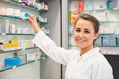 Junior pharmacist taking medicine from shelf at the hospital pharmacy