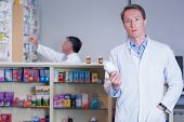 Concentrating doctor holding medicine jar in the pharmacy