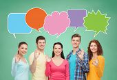 school, education, communication, gesture and people concept - group of smiling teenagers showing ok sign over green board background with text bubbles