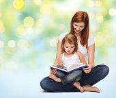 childhood, parenting and literature concept - happy mother with adorable little girl reading book over green lights background