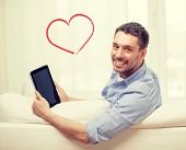 technology, home and lifestyle concept - smiling man working with tablet pc computer at home