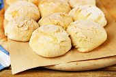 Fresh homemade bread buns from yeast dough on wooden board, on wooden background