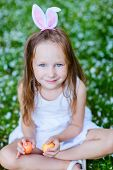 Adorable little girl wearing bunny ears playing with Easter eggs on a grass covered with white flower petals on spring day