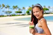 Green detox smoothie - woman drinking vegetable smoothie after fitness running workout on summer day. Fitness and healthy lifestyle concept with beautiful fit mixed race Asian Caucasian model.