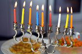 stock photo of hanukkah  - Hanukkah menorah lit with eight candles during dinner celebration at the last day of Hanukah - JPG