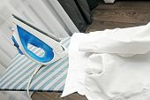White Collar Shirt And Iron On Ironing Board