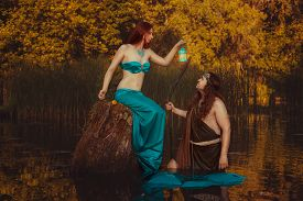 picture of undine  - Fairytale woman sitting on a snag in the swamp and shines a flashlight man - JPG