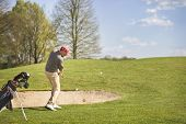 picture of golf bag  - Male golf player pitching ball in front of bunker - JPG