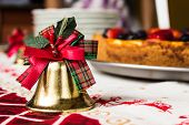 image of cheesecake  - Golden bell with green and red ribbons on top at a dinner table on a tablecloth with reindeers with an out of focus cheesecake on the background - JPG