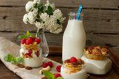 stock photo of breakfast  - yogurt for breakfast with nuts raspberry and milk - JPG