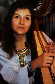 pic of celtic  - Young woman playing celtic harp in a white angelic historical costume - JPG