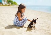 image of little puppy  - Little girl and little dog on the beach in sunny summer day near sea child with puppy outdoors - JPG