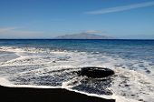 foto of discard  - An abandoned truck tire discarded on a black sand beach on the island of Fogo is filled by incoming waves of the Atlantic ocean - JPG