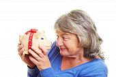 Retired Woman Looking At Piggy Bank