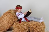 stock photo of haystack  - Ukrainian girl in national dress and blue jeans lying on a haystack and reading