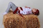 image of haystack  - Ukrainian girl in national dress and blue jeans lies on a haystack - JPG