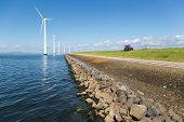 picture of dike  - Long row off shore wind turbines along the Dutch coast with a tractor mowing the grass of the dike - JPG