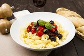 foto of olive shaped  - a close up image of cooked Italian pasta with tomato and olives - JPG