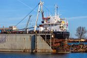 stock photo of shipyard  - A view of a large ship under repair in dry dock at a shipyard - JPG