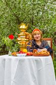 stock photo of curvaceous  - Beautiful Russian girl with a curvaceous rosy and happy sitting at a table with a samovar drying bagels budlikami strawberries in the spring blooming garden bright colors and spring - JPG