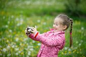 foto of dandelion  - Little smiling and curious girl photographing with her camera exploring nature and standing in a dandelion meadow - JPG