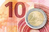 picture of ten  - Detail of two euro coin on red ten euro banknote background - JPG