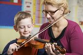 image of pupils  - Teacher Helping Pupil To Play Violin In Music Lesson - JPG
