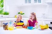 pic of healthy eating girl  - Little girl and boy preparing breakfast in white kitchen - JPG