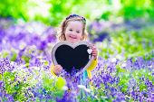 picture of little young child children girl toddler  - Child playing in bluebells forest - JPG
