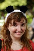 stock photo of pandas  - young woman in the foreground with panda ears headband - JPG