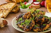 stock photo of chive  - Grilled teriyaki chicken wings with chive and microgreens on top garlic toast with fresh herbs and czech beer - JPG