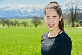 stock photo of snow capped mountains  - 14 year old Israeli teenager girl in the Switzerland country with green fields and snow - JPG