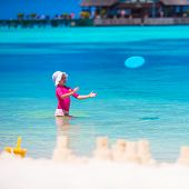 stock photo of frisbee  - Little girl playing frisbee on a tropical white beach - JPG