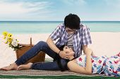 stock photo of caress  - Portrait of happy couple relaxing at the beach with the man caress his girlfriend - JPG