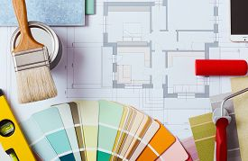 image of reconstruction  - Painter and decorator work table with house project color swatches painting roller brush and tools top view - JPG
