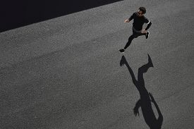 stock photo of sportswear  - Top view athlete runner training at road in black sportswear at central position - JPG