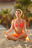 Young Woman In Orange Bikini Sitting On Beach In Lotus Pose With Closed Eyes And Meditating
