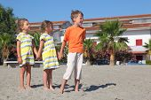 Little Boy And Two Girls Standing On Beach, Holding For Hands And Looking At Side