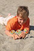 Caucasian Boy In Orange Shirt Lying On Beach, Multicolored Lollipops Stick Into Sand