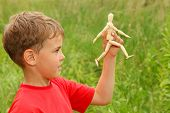 Boy In Red T-shirt Is Played By Wooden Little Manikin In Nature. Manikin Goes. Focus On Manikin
