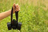 Children's Hand Holding Big Black Respirator On Background Of Green Grass