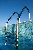 Shiny Chrome Ladder Into Pool, Blue Sky, Blue Water, Blue Bottom