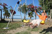 Little Girl Sitting On Swing At Playground, Sunny Day, Trees With Flowers And Sea