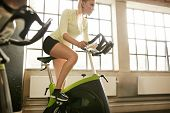 Woman Working Out On Gym Bike poster