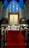 stock photo of peace-pipe  - church with red carpet stained glass windows and pipe organ - JPG